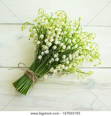 A bouquet of lilies of the valley on a wooden surface. Background with fragrant May lilies of the valley.