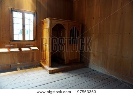 MACKINAW CITY, MICHIGAN / UNITED STATES - JUNE 18, 2017: A confession booth stands in the corner of the Church of Sainte Anne, in the Colonial Michilimackinac State Park.