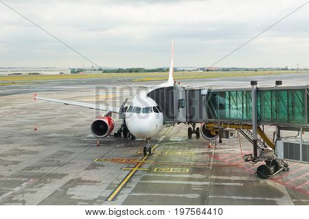 PRAGUE, CZECH REPUBLIC - JUNE 16, 2017: Aircraft with passage corridor or tunnel being prepared for departure from an international airport. Passengers boarding an airplane in a modern airport.