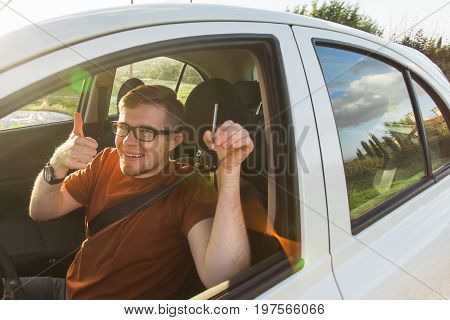 Young driver showing car keys and thumbs up happy. Man holding car key for new automobile. Rental cars or drivers licence concept with male driving in beautiful nature on road trip