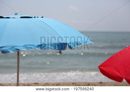 Blue And Red Beach Umbrellas On The Beach By The Sea In Summer