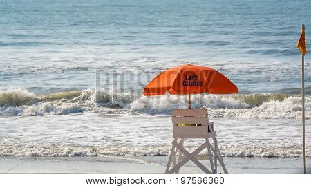 An empty lifeguard station at the ocean edge