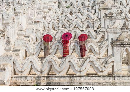 Back side of three buddhist burmese with traditional umbrella on the Mya Thein Tan Pagoda at bagan mandalay myanmar