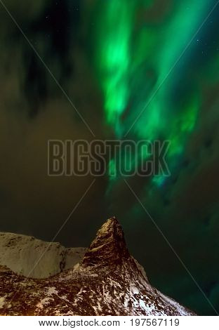 Aurora borealis over snowy islands from top view of Lofoten
