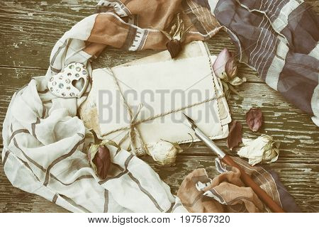 Vintage background with brooch heart shape pack of cards tied with rope on wooden table sepia toned