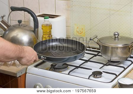 Preparation of fried eggs at home in the kitchen. Visual material. The process of breaking eggs into a hot frying pan