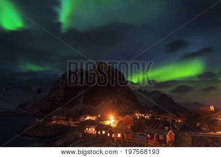 Aurora borealis over the mountain at the hamnoy village view point of Lofoten norway