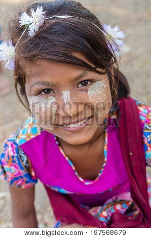 MANDALAY MYANMAR - MARCH 12 : Unidentified Burmese girl with traditional thanaka on her face on March 12 2016 in Mandalay Myanmar.Thanaka is a yellowish-white cosmetic paste made from ground bark