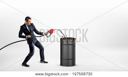A businessman holds a gas nozzle and overfills a black barrel with oil. Oil and gas industry. Oil procurement. Gas station business.