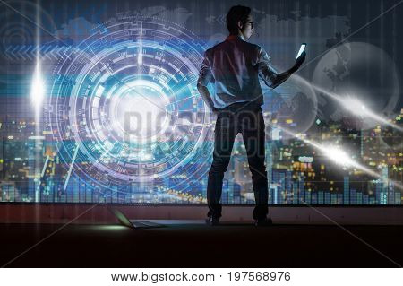Asian businessman standing and using the smart mobile phone showing with technology digital virtual screen over the cityscape background at night time Business technology and trading concept