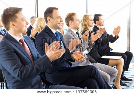 Audience of happy business people sitting at training room conference hall applauding to speaker