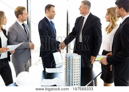 Business meeting of architects and investors shaking hands finishing deal model of modern multi storey residential building house on table