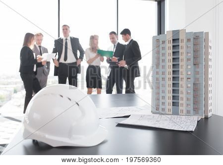 Business meeting of architects and investors model of modern multi storey residential building house and hardhat on table