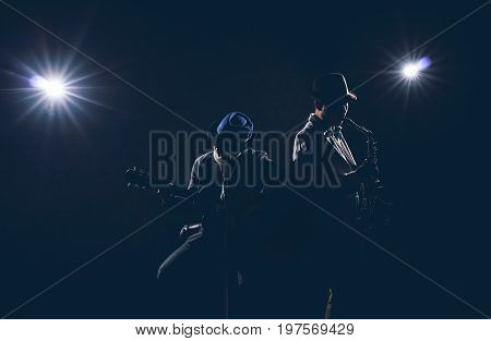 Musician Duo band playing a saxophone and singing a song and playing the guitar on black background with spot light and lens flare musical concept