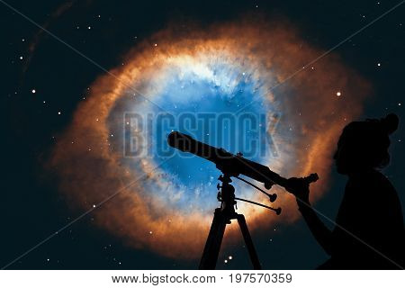 Girl Looking At The Stars With Telescope. The Helix Nebula Or Ngc 7293 In The Constellation Aquarius