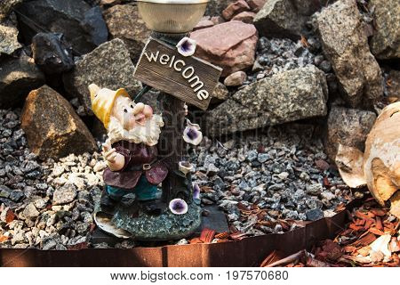 a handmade statue of a small gnome in a garden