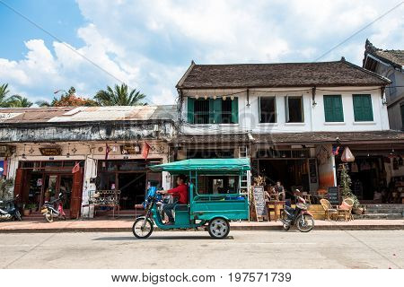 LUANG PRABANG LAOS - MARCH 11 2017: Horizonal picture of restaurants and stores at Sisavangvong Road located in the olf Quarter of Luang Prabang Laos. Tuk tuk and motorcycles.