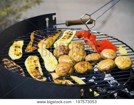 Grilling vegetables on chargrill. Barbecue. Cooking vegetables on the grill pan in a herb marinade, top view. Delicious vegetable barbecue on grill.