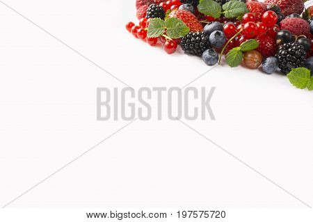 Ripe strawberries blueberries raspberries blackcurrants and red currants mint. Berries at border of image with copy space for text. Background berries. Top view. Various fresh summer berries on white background.