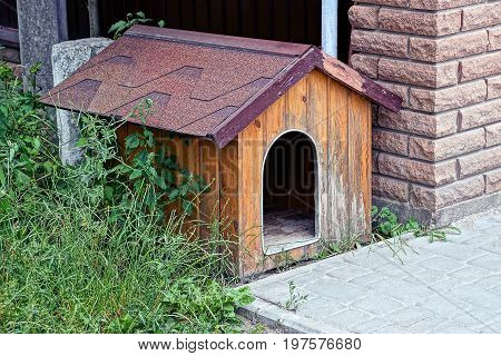 Empty brown dog house near a brick wall in the grass
