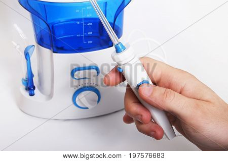 man's hand holds the handle of oral irrigator with an individual toothbrush. Side nozzles for tongue delicate cleansing sensitive gums. Dentists recommend taking care of teeth cavity irrigator.