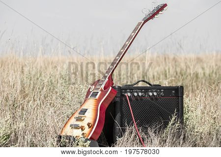 electric guitar and amp on the field the concept of music and creativity