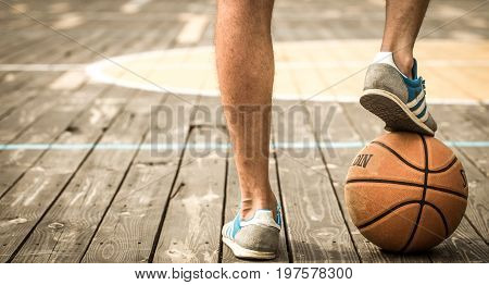 A Young Man With A Basketball On The Court