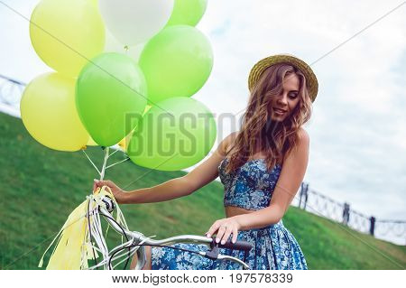 Portait of beautiful woman wearing a nice blue dress having fun in park with bicycle and ballons. Vintage scenery. Pretty girl with retro look, bike and ballons.