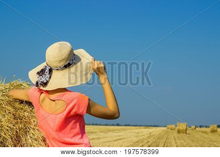 Happy woman on hay stack in sunny day. Beauty romantic girl outdoors against hay stack. Photo of sexy brunette in a field with haystacks