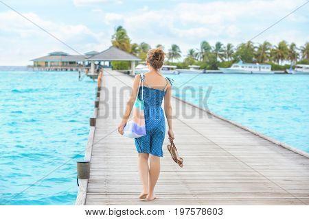 Beautiful young woman walking along pontoon at sea resort