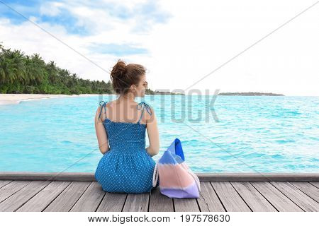 Beautiful young woman sitting on pontoon at sea resort