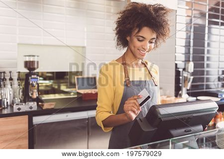 Payment process. Charming pleasant girl is making transaction with credit card and smiling while standing against cash desk in organic shop. Copy space in the left side