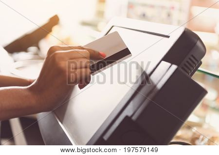Close-up of hands of young  woman is holding bankcard and making transaction. She is standing at cash desk in sunny organic store
