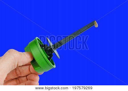 Spare parts Engine Oil Dipstick with drop oil. The gauge of level of oil in the car. Isolated blue background