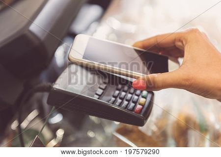 Pay by phone. CLose-up of young african woman hands is paying with nfc technology using mobile phone