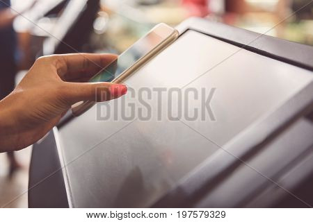 Modern technology. Close-up of hand of african woman is holding smartphone while scanning screen of cash desk