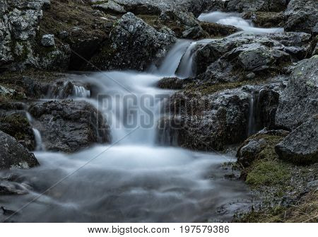 Small waterfall on mountain river Zagedanka. Landscape in gray tone. Caucasus mountains.  Karachay-Cherkessia. Russia.