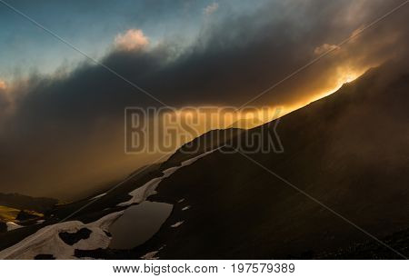 Sunset on mountain lake. Evening landscape. Photo through clouds. Caucasus mountains. Karachay-Cherkessia. Russia.