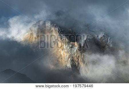 Mountain peak peeking through clouds in Caucasus mountains. Rock Zagedan. Karachay-Cherkessia. Russia.