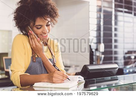 Client call. Positive young mulatto girl is taking order for organic food on mobile phone while standing at glass counter and writing to journal with smile. Copy space in the right side