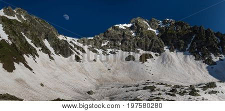 Moon rises over snow pass Zagedan lake. Caucasus mountains. Karachay-Cherkessia. Russia.