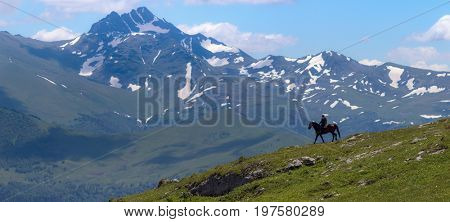 Mountain landscape and shepherd on horse. In the background - mount Magisho. Caucasus mountains. Karachay-Cherkessia. Russia.