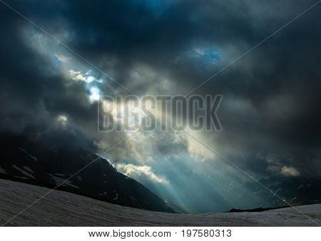 Rising sun is breaking through clouds over ridge Abushura Akhuba in the wake of a storm. Dramatic overcast sky. Caucasus mountains. Karachay-Cherkessia. Russia.