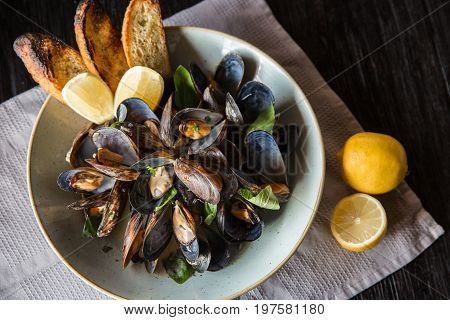 Mussels in stoneware bowl with lemon on wooden dark background