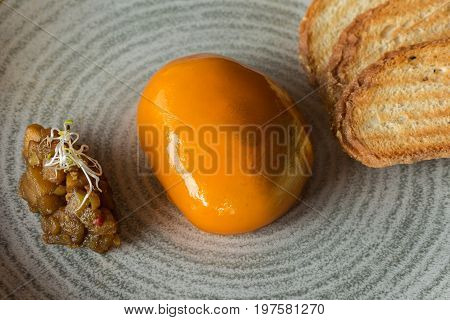 Pate of duck on a plate with croutons on a stoneware plate.
