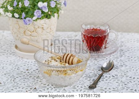 Healthy breakfast. Cup of karkadeh red tea cottage cheese plus oat flakes linseed and honey.