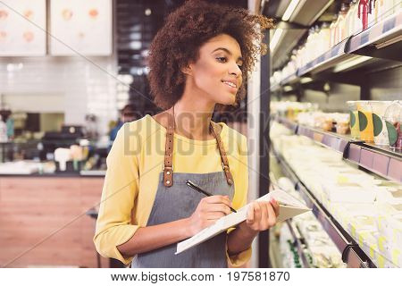 Busy at work. Pleasant attractive waitress is holding journal and making notes while being involved in job at vegan food market