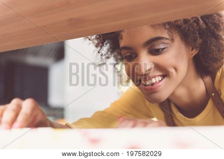 Where is it. Close-up of cheerful attractive mulatto girl is laboring in organic food store with pleasure