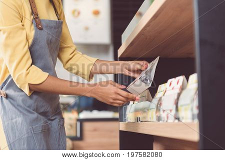 Tasty meal. Close-up of arms of responsible female worker. She is holding small package of food while standing in vegan store