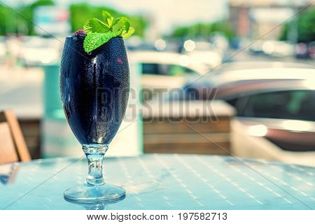 Close up glass with black original cocktail garnished with mint and raspberry with blue wooden background